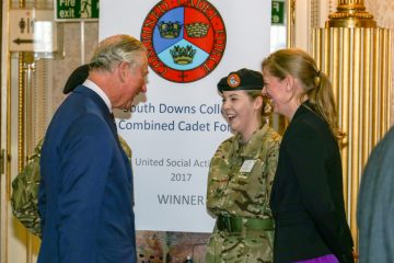 Student cadet in uniform laughing with HRH Prince Charles