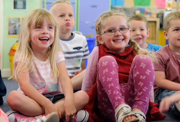 nursery age children sitting on the floor smiling
