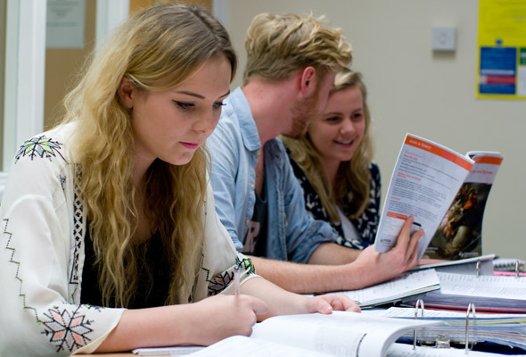 three students studying with books