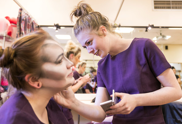 female student putting theatre make up on fellow student