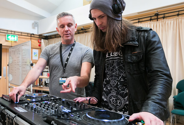 student and teacher using DJ decks