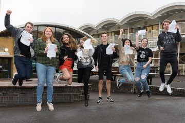 HSDC results day - students holding results papers and jumping with joy