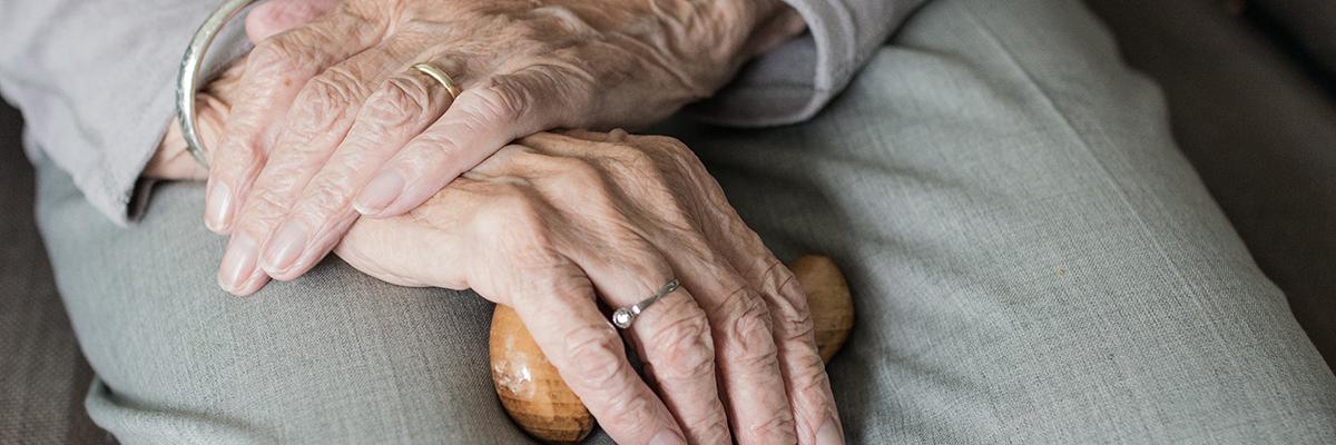 closeup of an elderly persons hands holding a walking stick