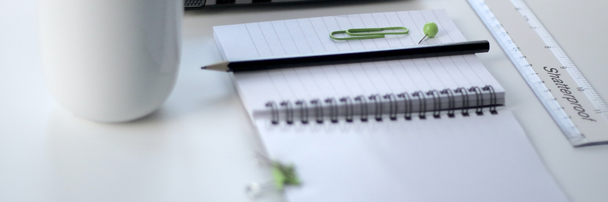 close up of a notebook, pencil, ruler and cup of coffee