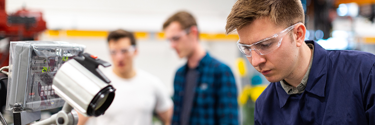 men in an engineering workshop wearing protective goggles