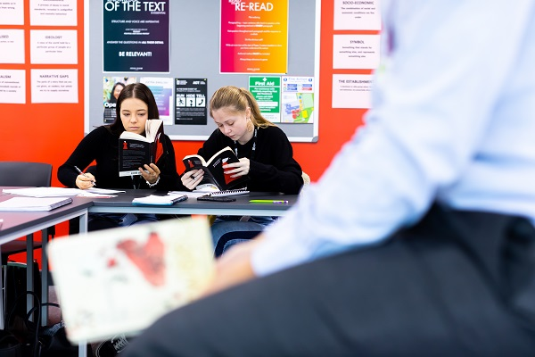 two female students reading books in class