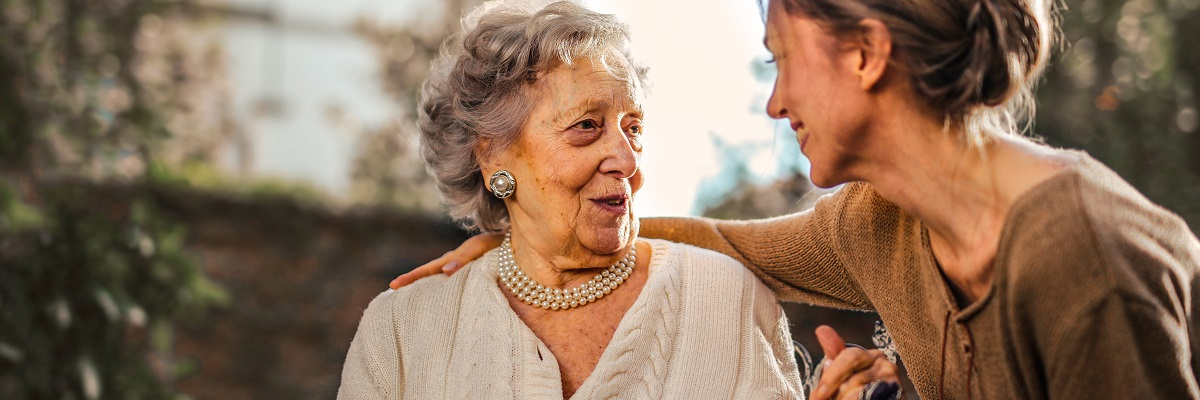 a women embracing and holding hands with an elderly woman in a wheelchair