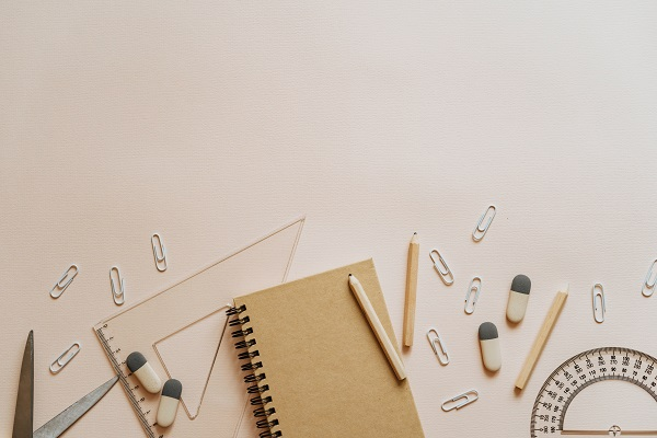 a notepad, pencils, rubbers, paper clips, ruler and protractor on a desk