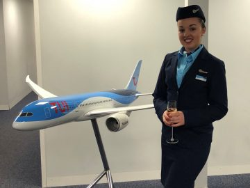 Former HSDC student in Air Cabin Crew uniform standing in front of model plane