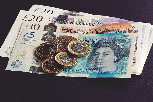 Twenty, Ten and five pound notes in pile with two and one pound coins on top