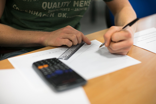 a student using a ruler, pencil and paper with a calculator