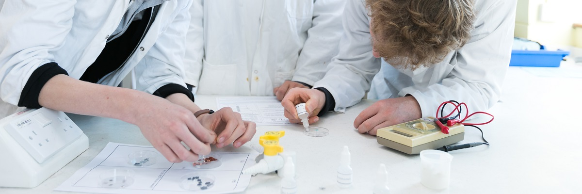students working with chemicals in lab coats