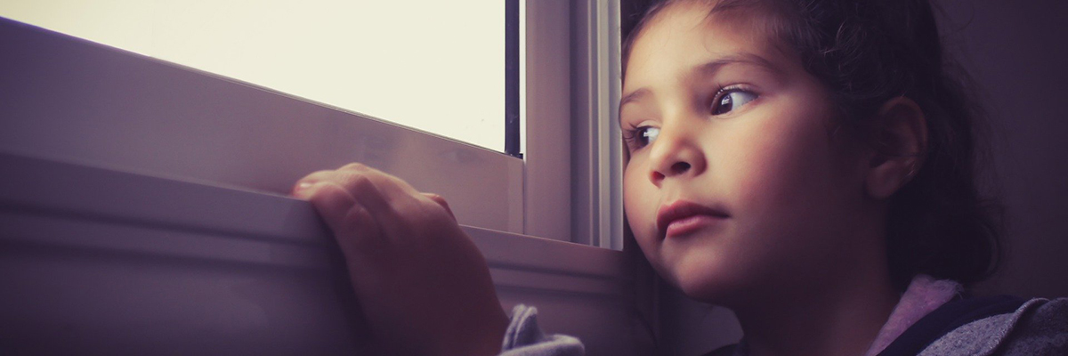 a child looking out of a window in thought