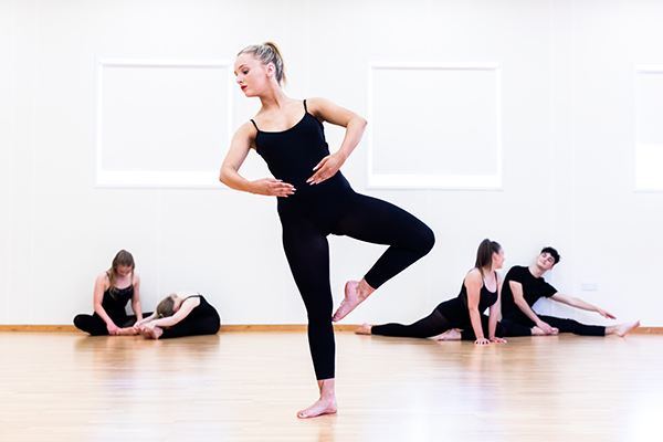 students in dance class, dancing and stretching