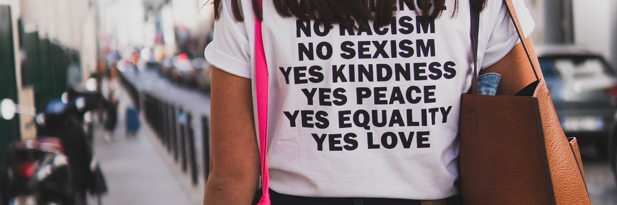 a woman wearing a t-short saying no racism, no sexism, yes peace, yes equality, yes love.