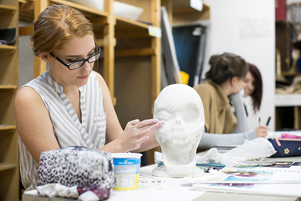 a student working on a clay art piece