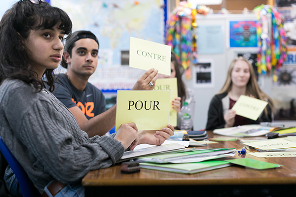 students holding up french words in class