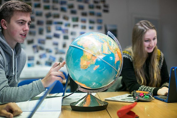 a student pointing at a globe