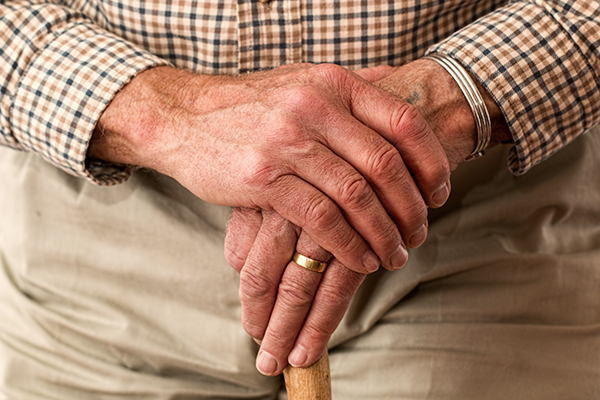 an elderly persons hands holding a walking stick