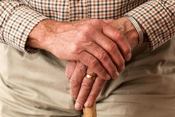 an elderly persons hands holding a walking stick