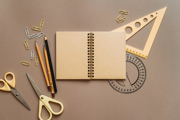 notebook, pencils, scissors, ruler and protractor on a desk