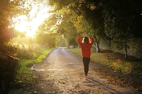 a woman in fitness gear about to run down a path with the sun ahead