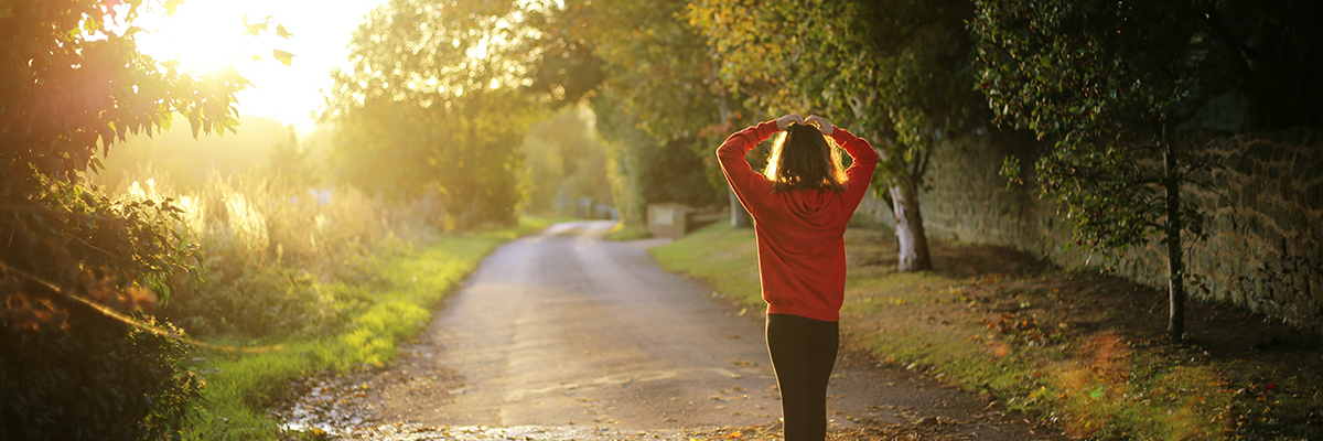 a woman in workout clothes looking into a sunny road ahead