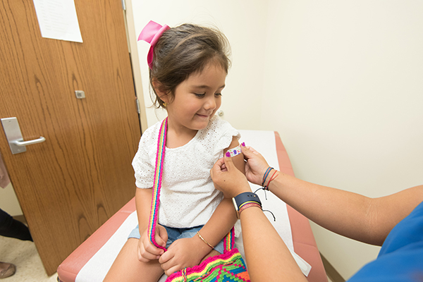 a child having a plaster applied to their arm