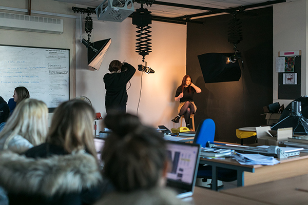student taking a photo of someone in a photography studio