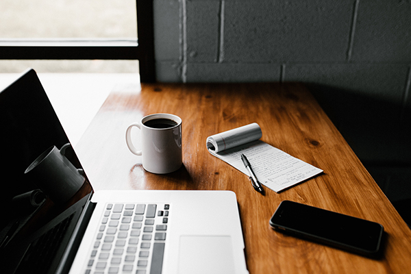 a laptop, pen, paper, mobile phone and cup of coffee on a table