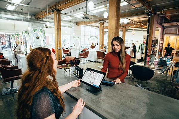 a women serving a customer at a till