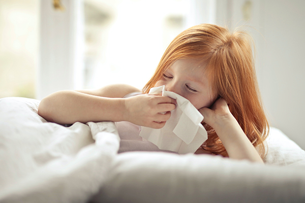child sneezing into a tissue