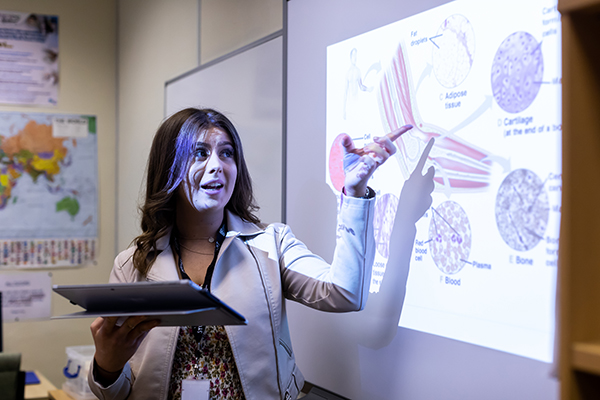 a student in front of a projector screen
