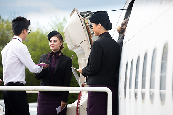 air cabin crew welcoming people into the cabin