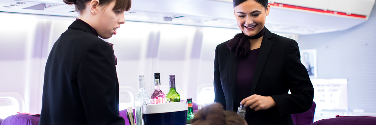 air cabin crew carrying beverages in a plane