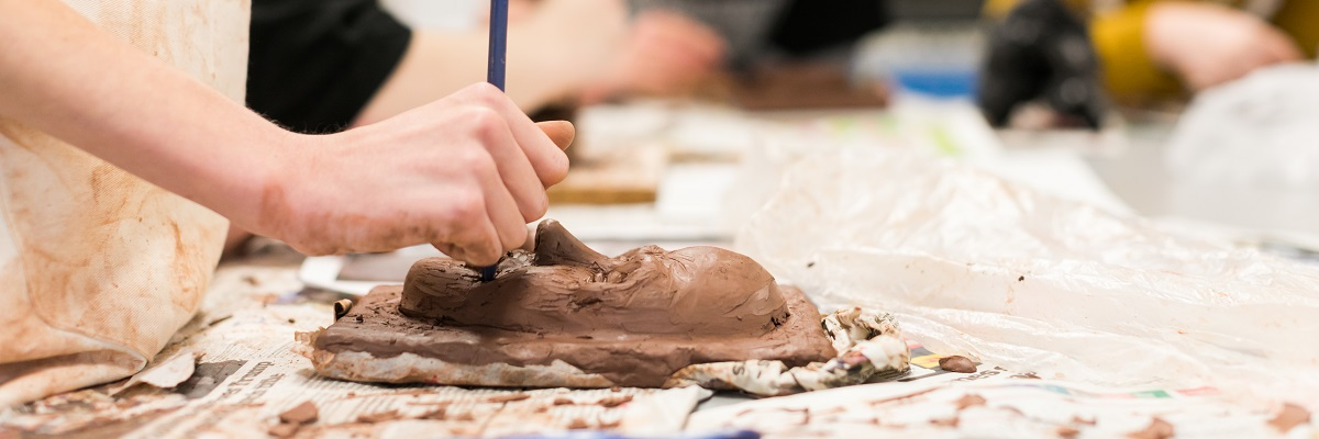a student working on a clay sculpture