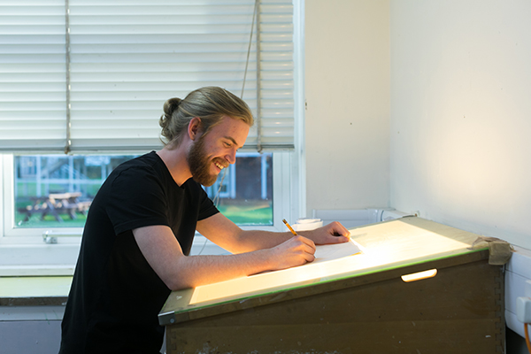 a male student working at a drawing desk