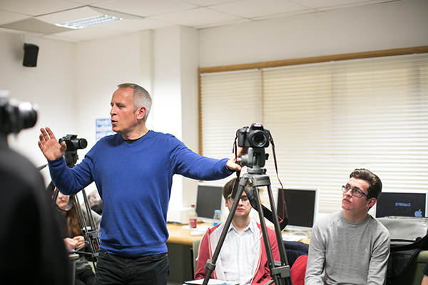 a lecturer talking to a class with a camera on a tripod
