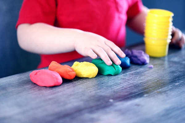 young child playing with different colour playdough