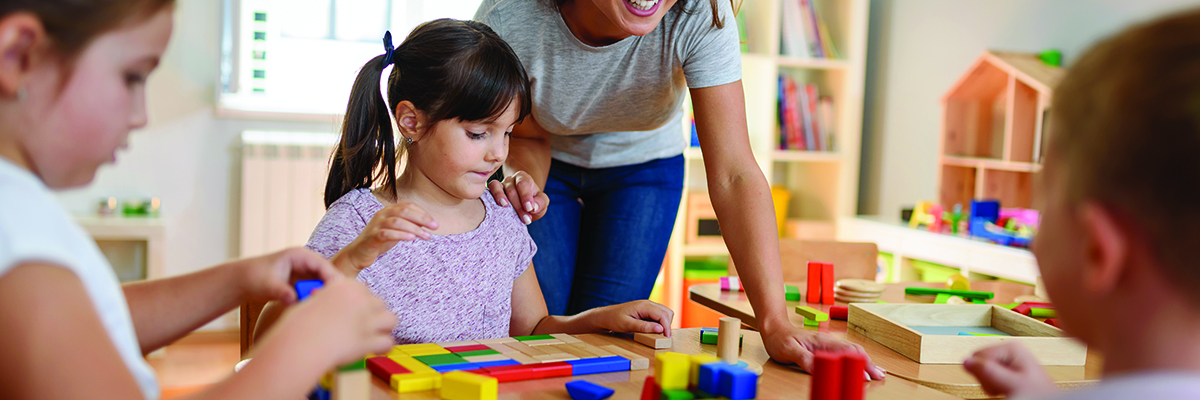 Preschool teacher with children playing with colorful wooden didactic toys at nursery