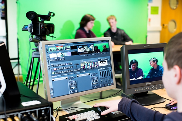 computer screen showing video editing software with a camera and green screen in background