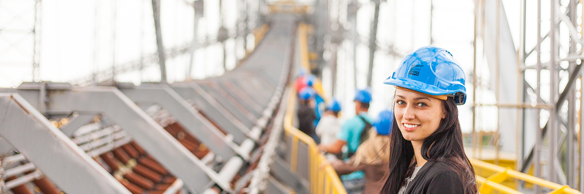 a woman wearing a hard hat on a structure
