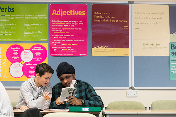 two students looking at a book together
