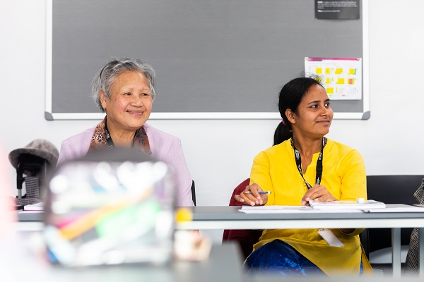 two ESOL students listening and smiling in class