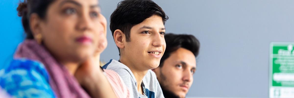 three ESOL student listening in class