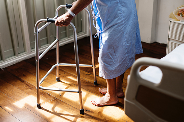 an elderly person using a zimmer frame