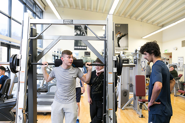 students in the college gym using equipment