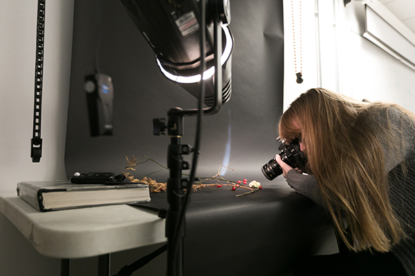 a student taking a photo in a photography studio