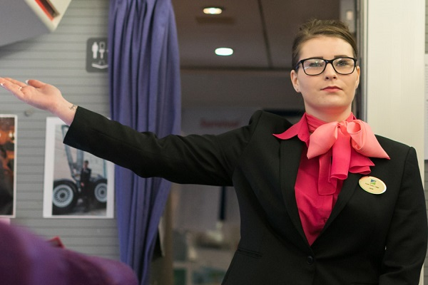 An air cabin crew student pointing towards emergency exit on a plane