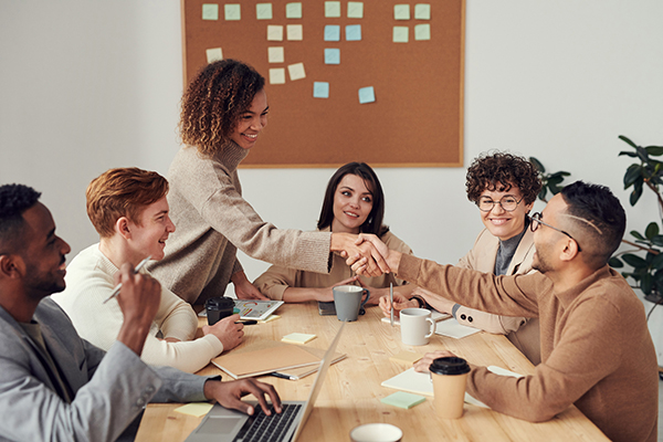 a women shaking a mans hand in front of a team of people at a table in a meeting